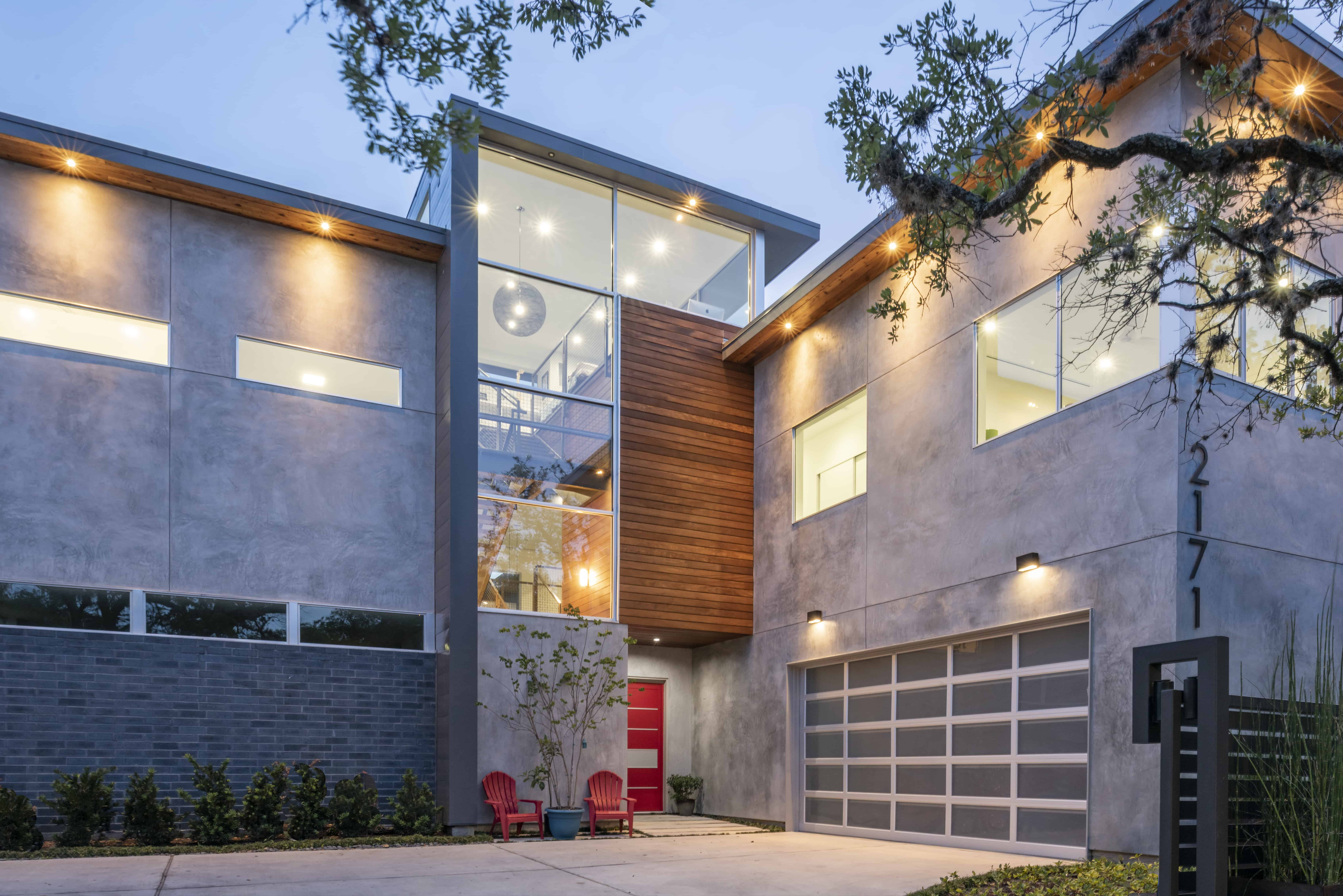 university boulevard modern home family lifestyle facade with natural stucco brick and wood glass garage door