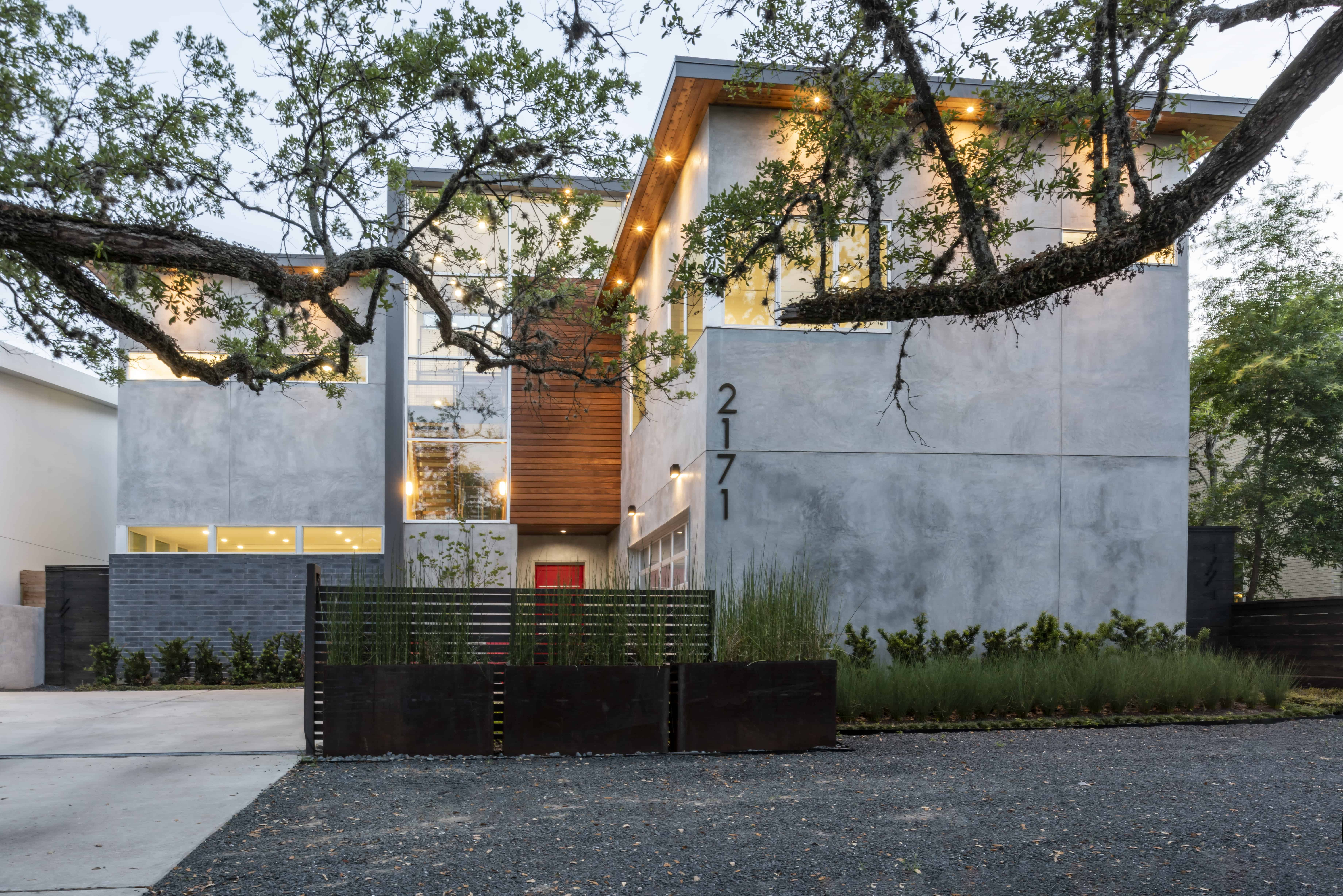 university boulevard modern home family lifestyle facade with natural stucco brick and wood