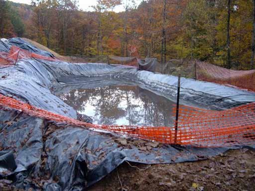 """Figure 9. Drilling pit. After it is full of cuttings and chemicals it is folded over (""""toxic burrito"""") and either buried or hauled off"""
