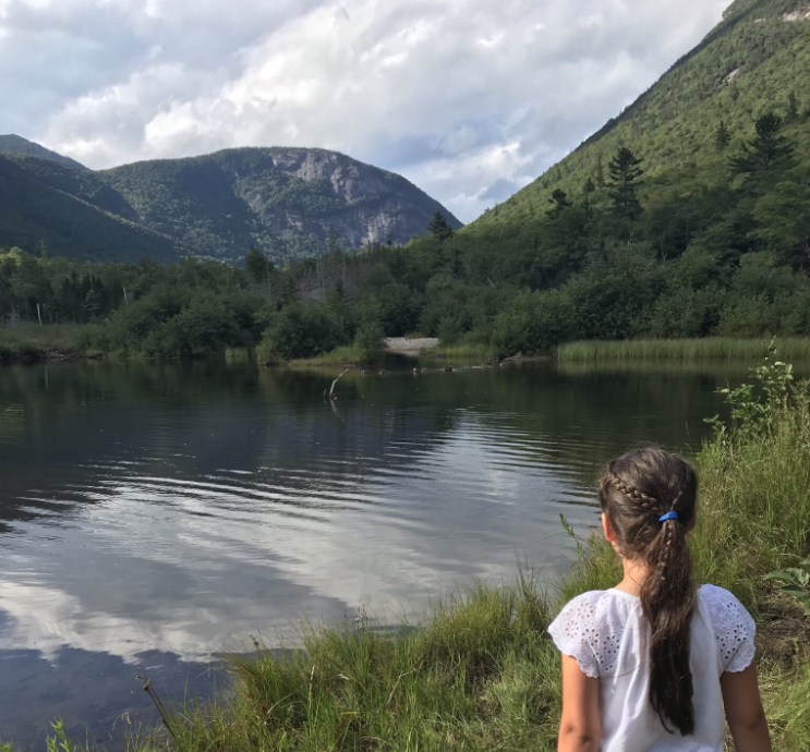 A young child looks at a body of water and mountains