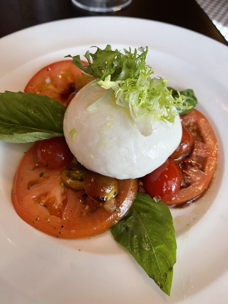 In-house made Burrata with tomatoes and basil form Trattoria al Forno.
