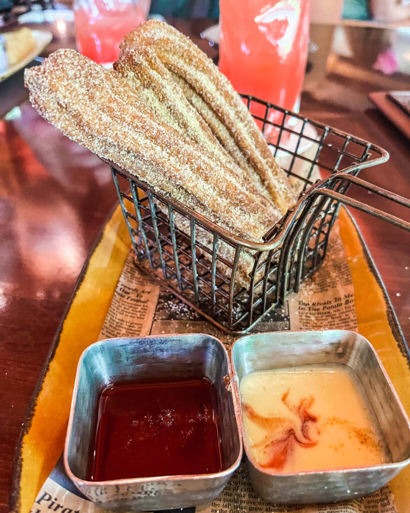 Churros in a basket with two dipping sauces in front, a chili-strawberry and a Vanilla Crema