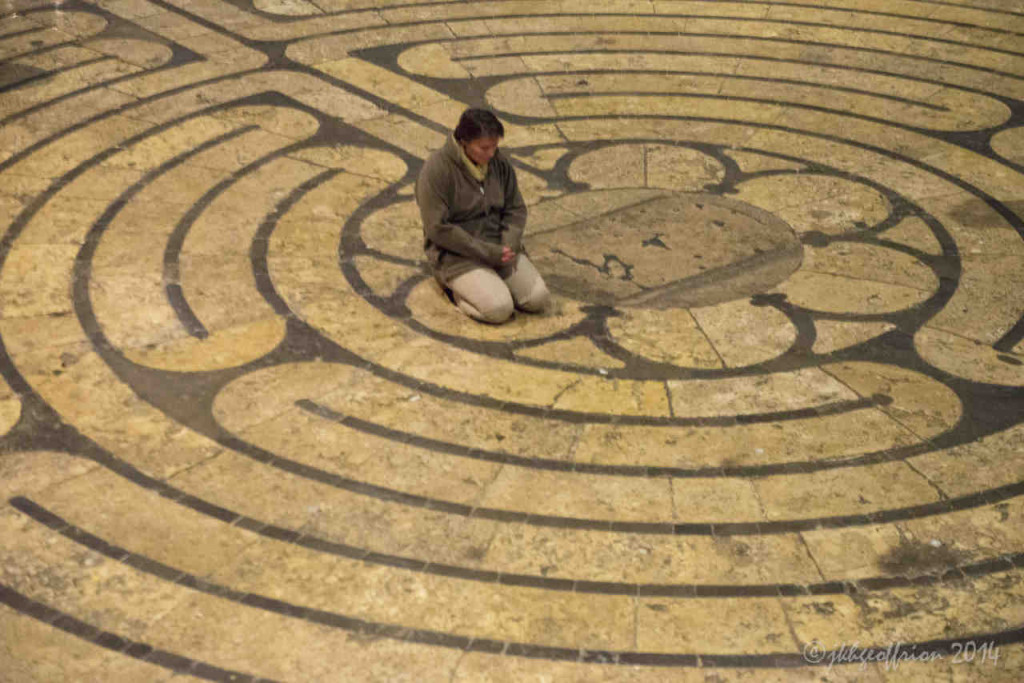 Praying in the center of the Chartres labyrinth by photographer Jill Geoffrion