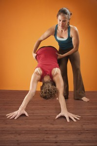photo of yoga teacher guiding student