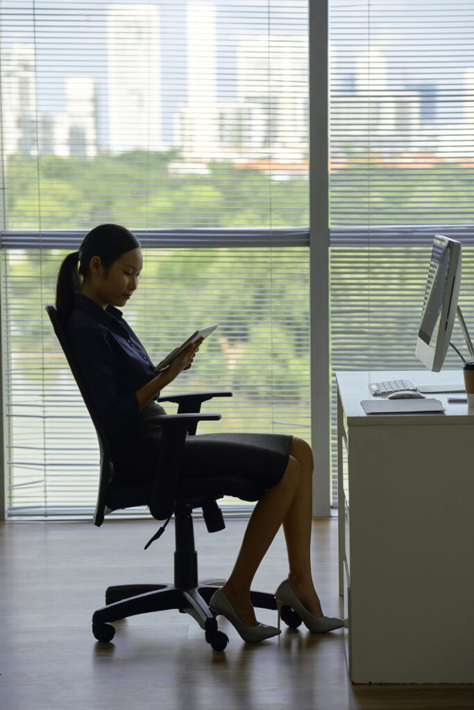 Elegant young Asian business lady sitting in office armchair and reading article on tablet computer
