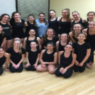 A group of girls in black leotards at a dance studio with their teacher Christina Caravella