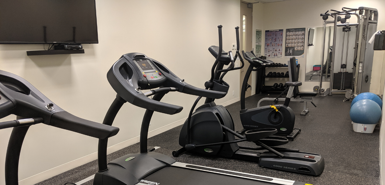 Bennington's one-site fitness room is shown. There's a wall-mounted TV, two treadmills, an elliptical, a stationary bike, free weights, a LifeFitness weight machine and a couple of exercise balls.