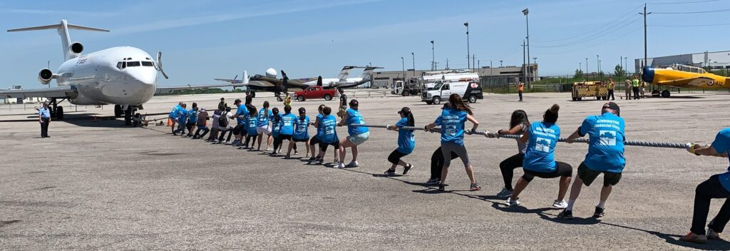 This is a photo of some Bennington team members all pulling on a large rope in unison. The large rope is attached to a plane. They are on the concrete of a tarmac with a white plane in the background. The sky is blue.