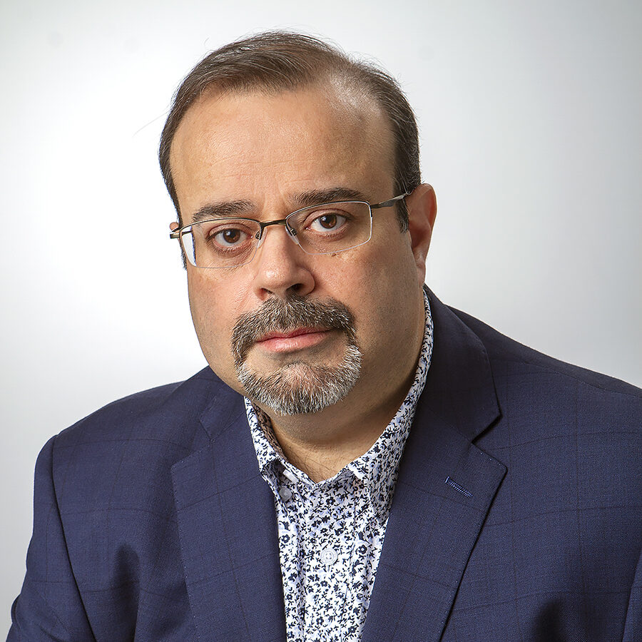 Joe is wearing a white shirt with a blue floral design, under a navy jacket. glasses and has a goatee. He is wearing a He is looking at the camera with a slight smile