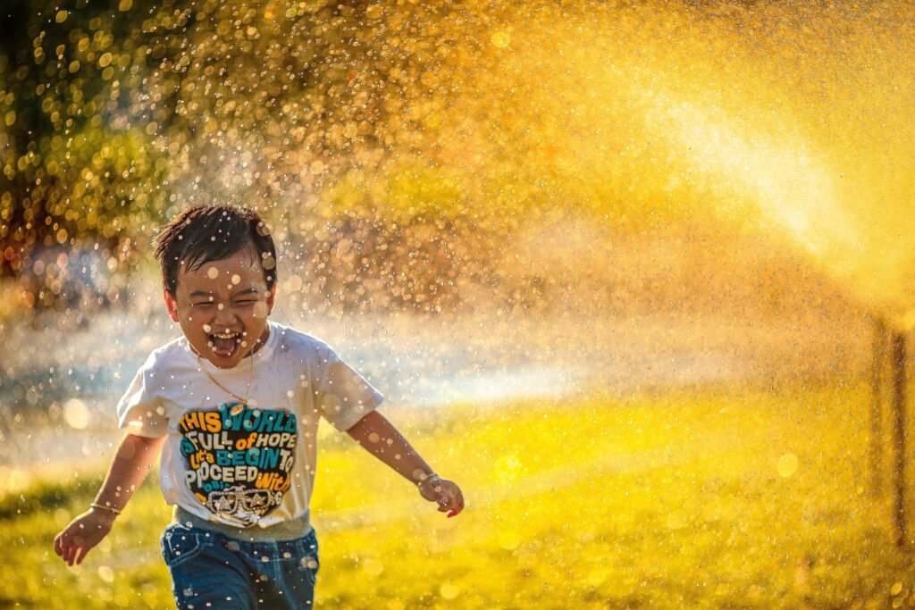 Image of a little boy running through a sprinkler to illustrate the joy of not having adhd symptoms in kids.