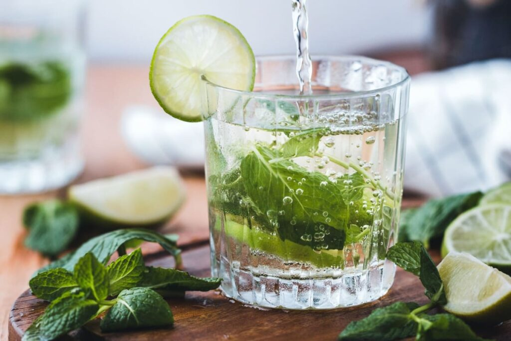 A picture of sparkling glass, lime and mint as a way to drink more water.