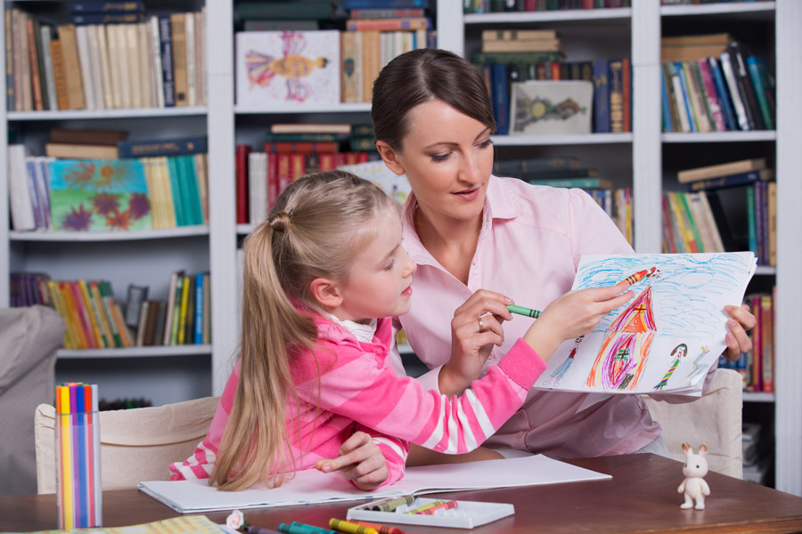 speech therapist working with a child in a school library