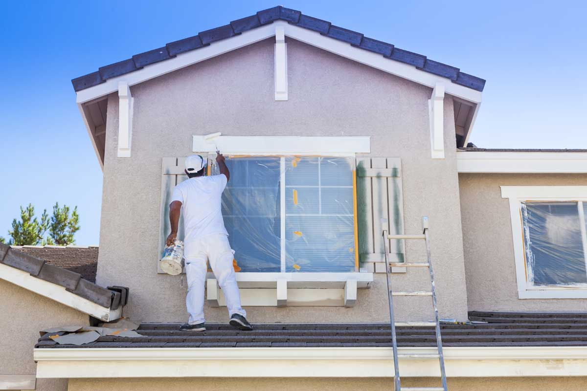 Residential painter painting the exterior window trim of a house