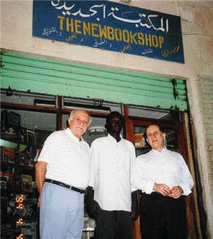 Ο Παναγιώτης Φλαγγίνης (αριστερά) με τον πρεσβευτή της Ελλάδας στο Χαρτούμ ποιητή Γιώργο Βέη και έναν σουδανό υπάλληλο, μπροστά στο βιβλιοπωλείο