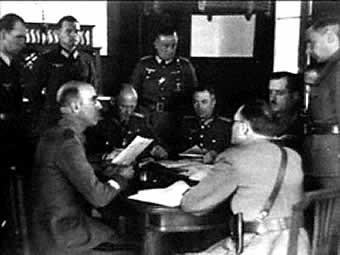 Ο αντιστράτηγος Γεώργιος Τσολάκογλου (καθιστός δεξιά) συζητά με τον γερμανό στρατηγό Γιοντλ (καθιστός δεύτερος από αριστερά) και τον ιταλό στρατηγό Φερρέρο (προς τα δεξιά με την πλάτη προς τον φακό) το τρίτο και οριστικό πρωτόκολλο παράδοσης της Ελλάδας στην ναζιστική Γερμανία και την φασιστική Ιταλία. Θεσσαλονίκη, 23 Απριλίου 1941. (Φωτο Κέντρου Σιμόν Βιζενταλ)