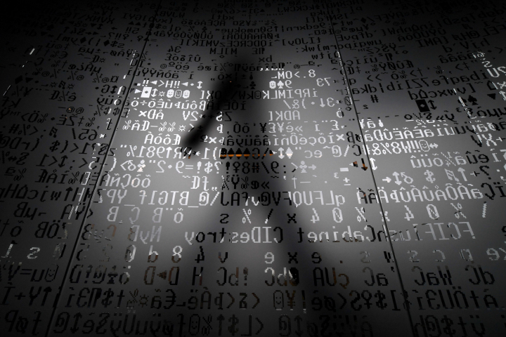 TOPSHOT - A picture taken on October 17, 2016 shows an employee walking behind a glass wall with machine coding symbols at the headquarters of Internet security giant Kaspersky in Moscow. / AFP / Kirill KUDRYAVTSEV / TO GO WITH AFP STORY BY Thibault MARCHAND        (Photo credit should read KIRILL KUDRYAVTSEV/AFP/Getty Images)