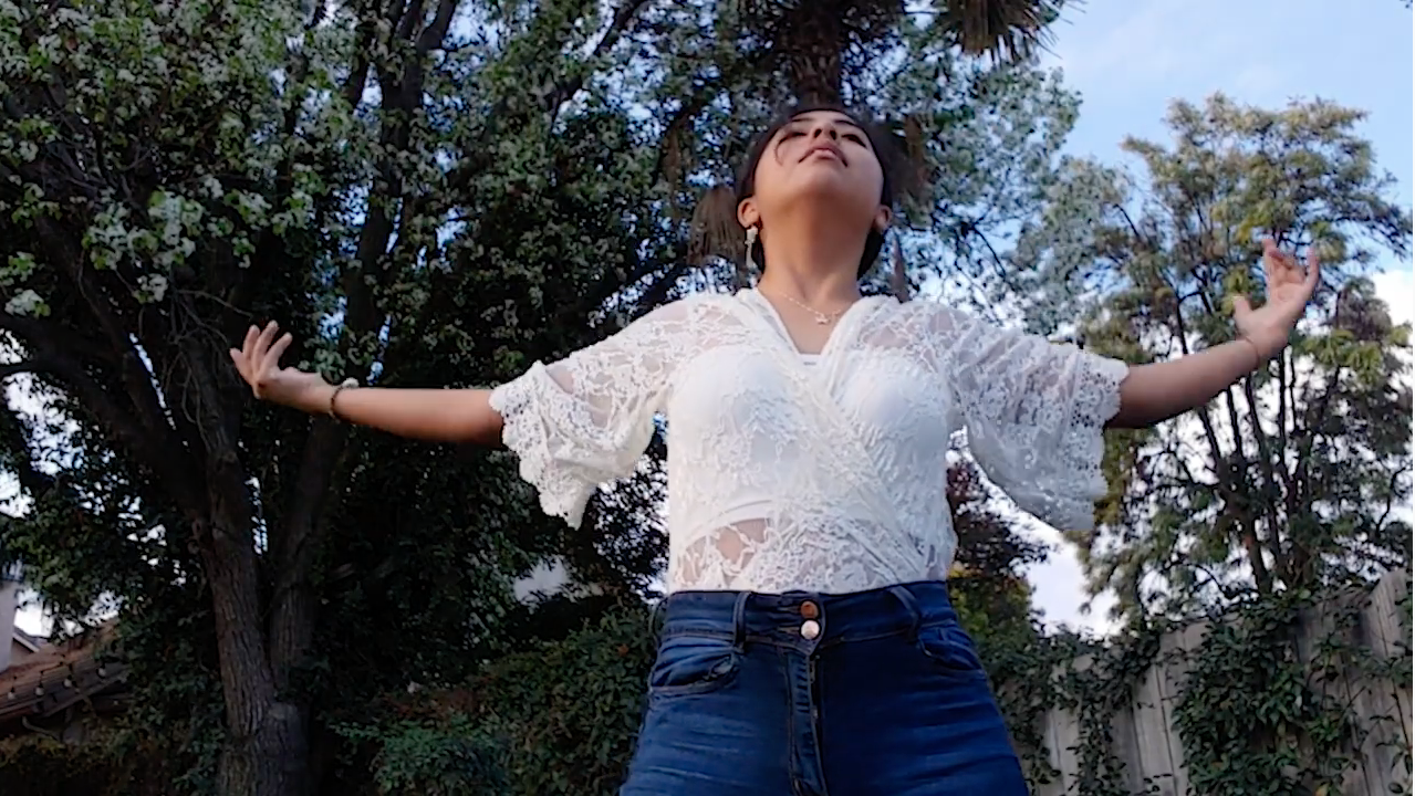 Teen dancing with arms wide open toward the sky