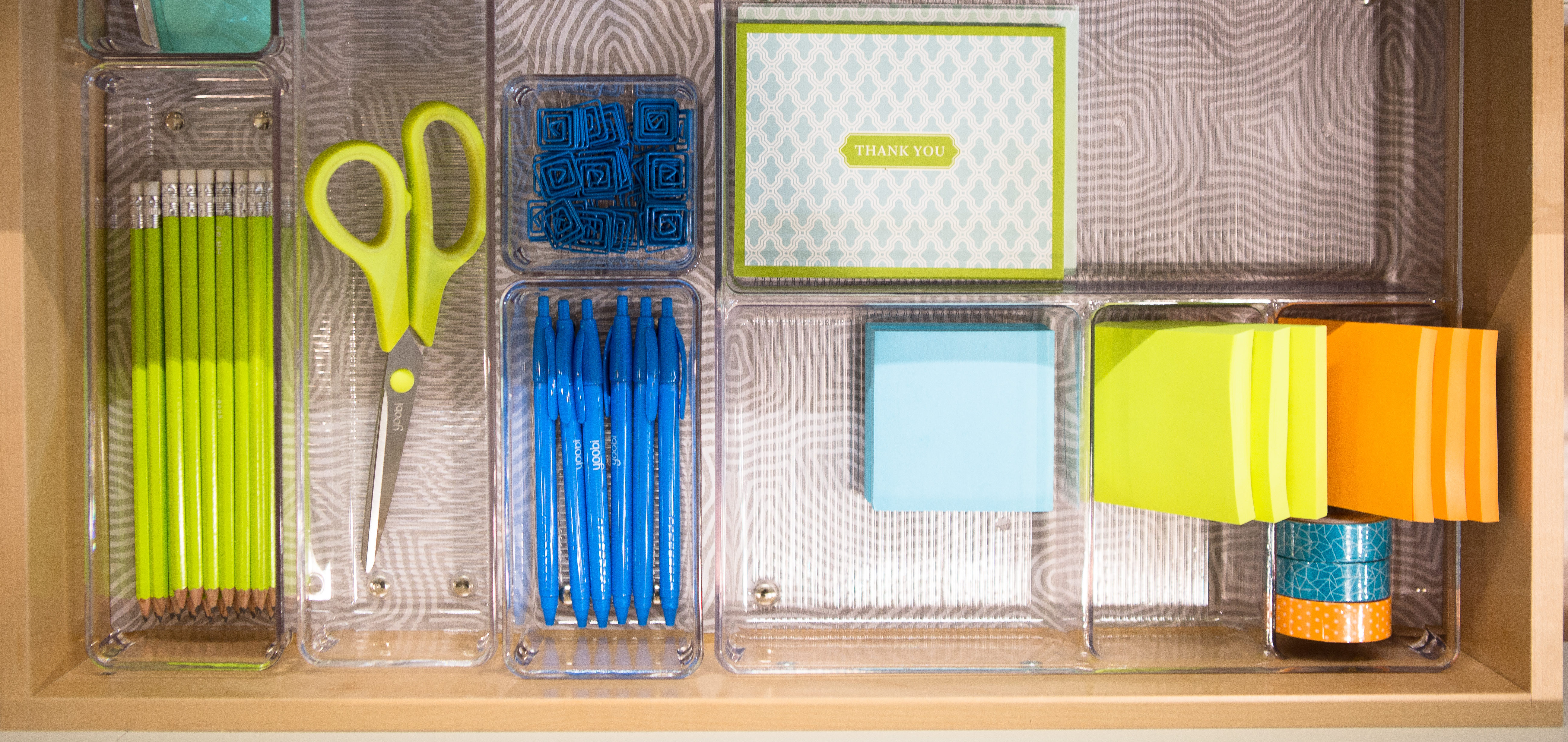 organized office drawer with sticky notes and scissors