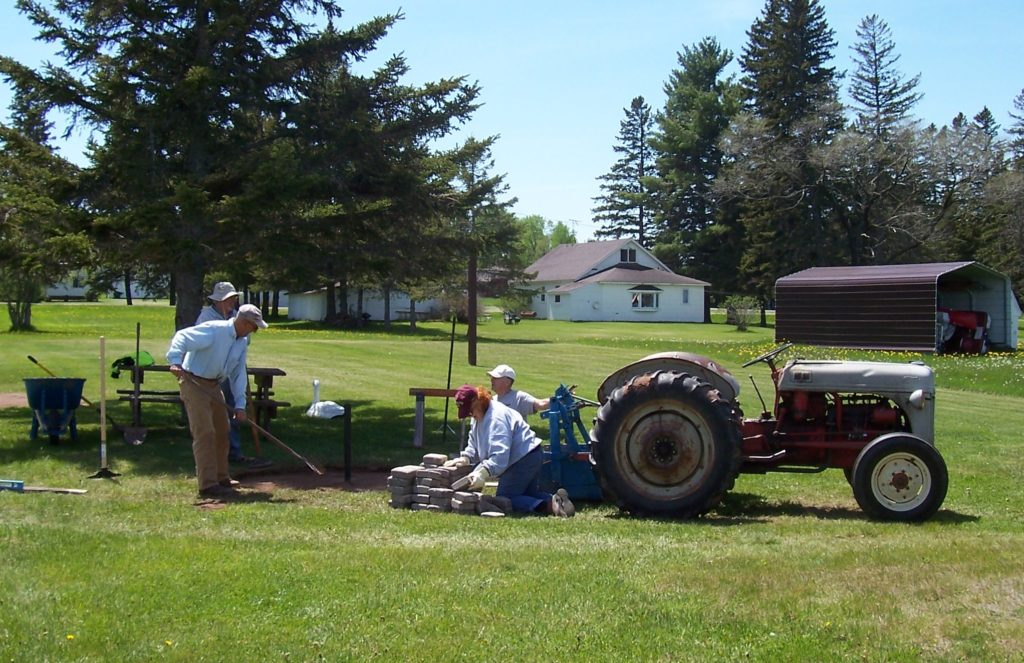 Volunteers placing pavers for grills at playground