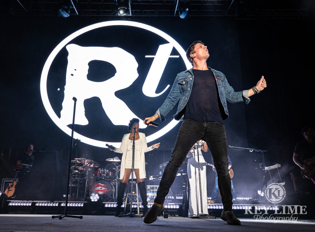 Iconic Rob Thomas photo, denim jacket and black jeans, backup singers and monochromatic stage design, giant RT logo