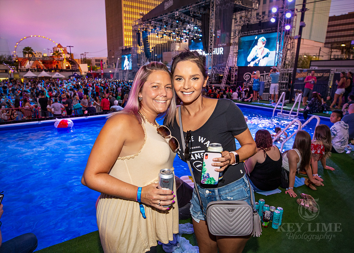 Two tan girls in their 20s smiling and holding a beer with a pool and outdoor festival stage in the background. Event photography of Bite of Las Vegas food festival