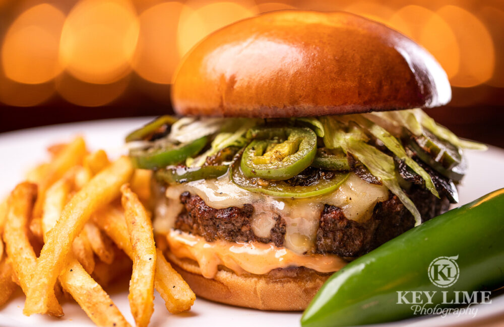 Las Vegas jalapeno gourmet hamburger with seasoned fires. This food photographer image feels warm and lively. Colors are not flat and boring.