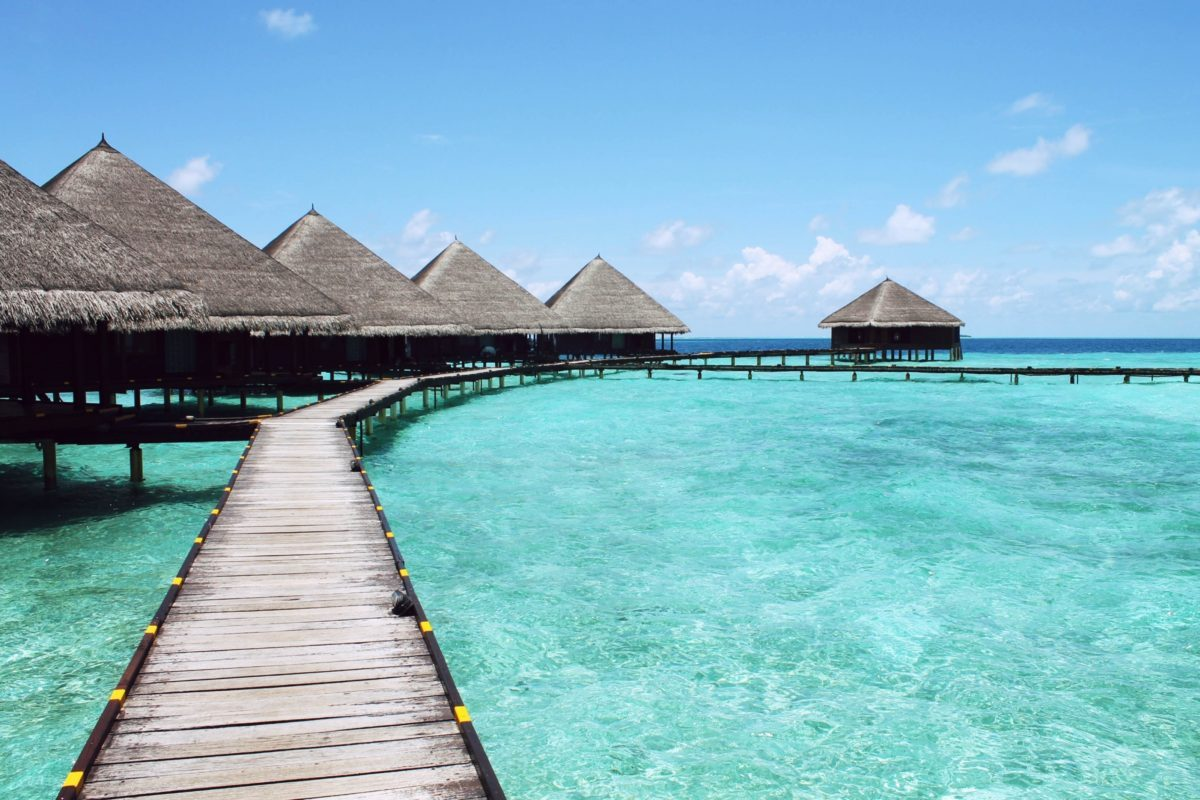 Maldives _ wooden-pier-and-palapas-above-turquoise-sea