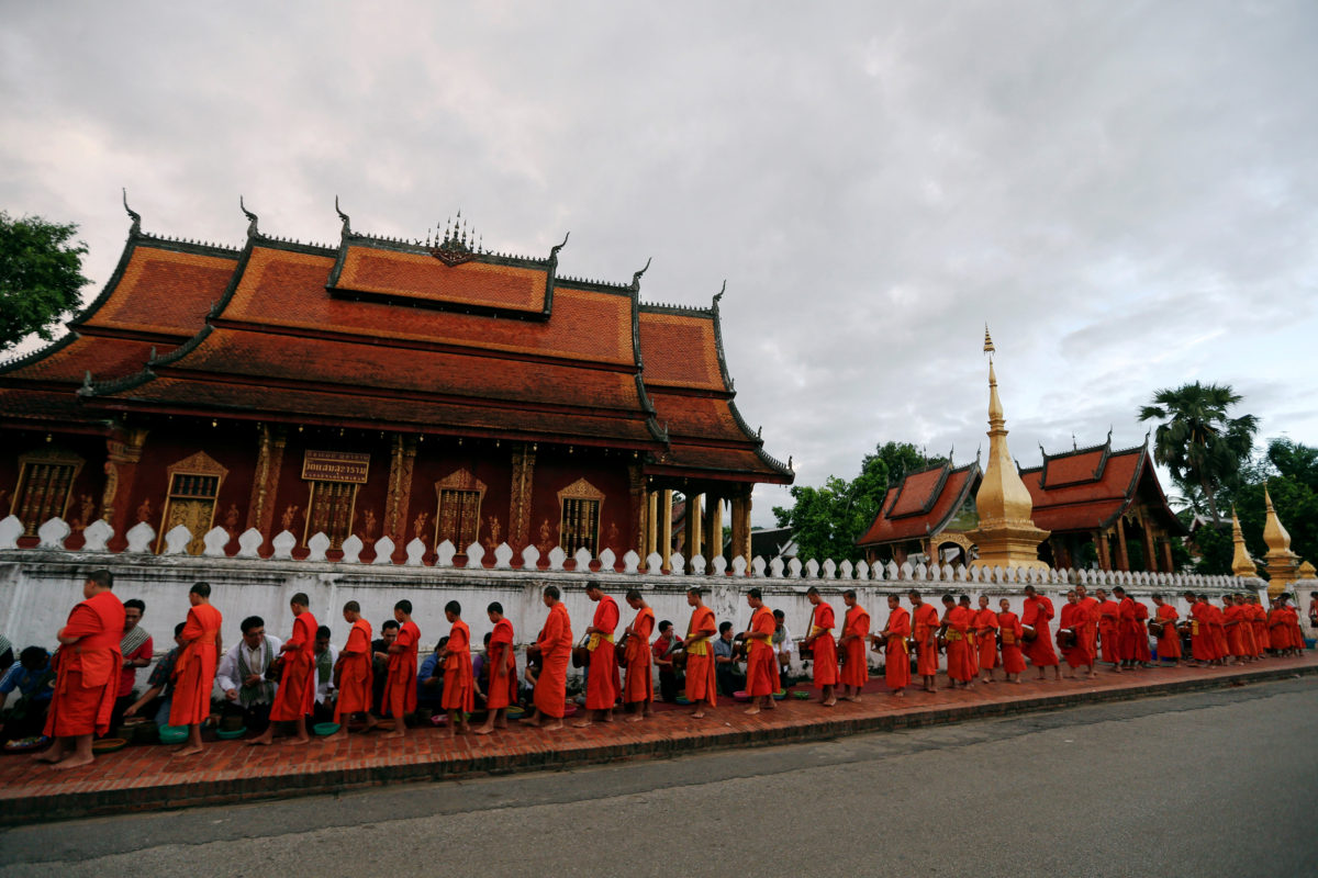 "Buddhist monks walk while collecting alms early morning in front of Wat Sene Buddhist temple in Luang Prabang, Laos July 31, 2016. REUTERS/Jorge Silva       SEARCH ""LUANG"" FOR THIS STORY. SEARCH ""WIDER IMAGE"" FOR ALL STORIES.  TPX IMAGES OF THE DAY"