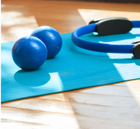 Pilates rings and therapy balls on a yoga mat