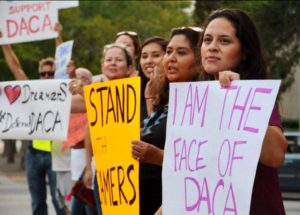 women holding signs supporting DACA