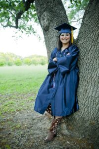girl with graduation cap and gown standing against a tree