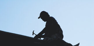 silhouette of roofer hammering on roof