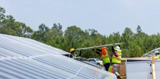 working men installing solar panels