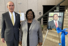 Mayor Sandy Stimpson and Jeanette Manzie standing by a photo of Councilman Manzie