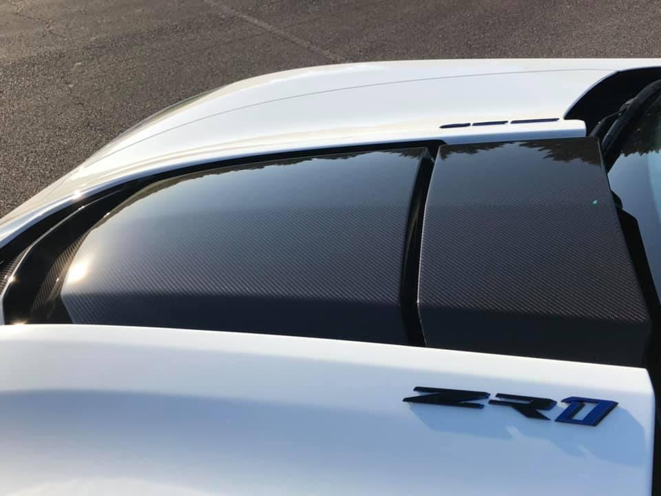 Black hood scoop of a white Chevrolet Corvette car
