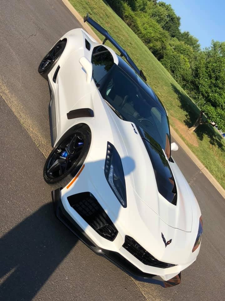Clean white Chevrolet Corvette car with a black spoiler and hood scoop