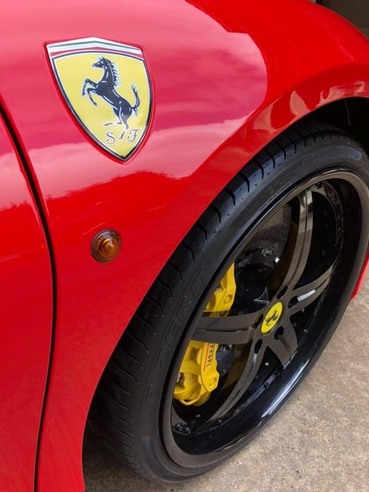 Ferrari logo and wheel on a shiny red car