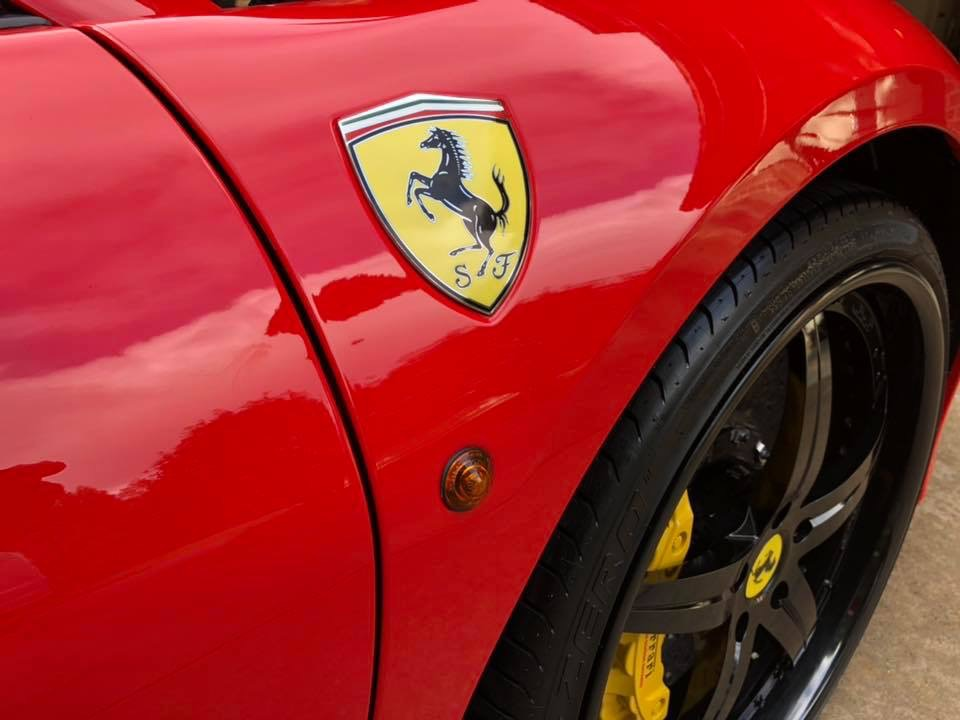 Ferrari logo and wheel on a clean red