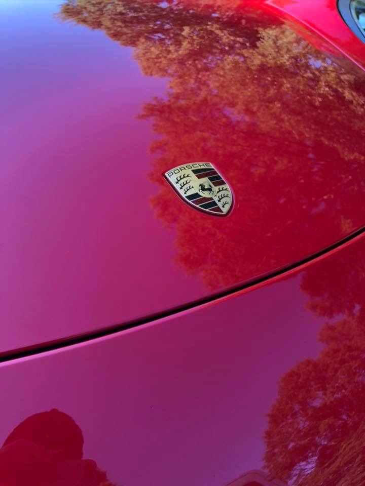 Porsche logo on a shiny red car