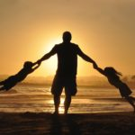 father palying with kids at the beach