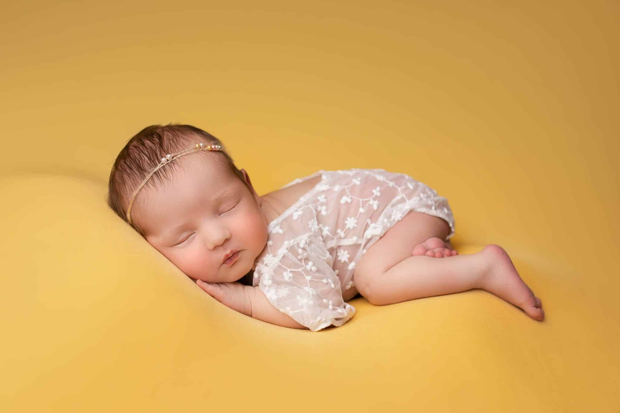 Baby girl sleeping on yellow blanket while wearing a cream lace romper.