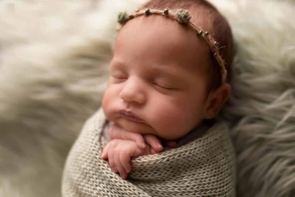 Baby girl wrapped in green wrap and a floral crown.