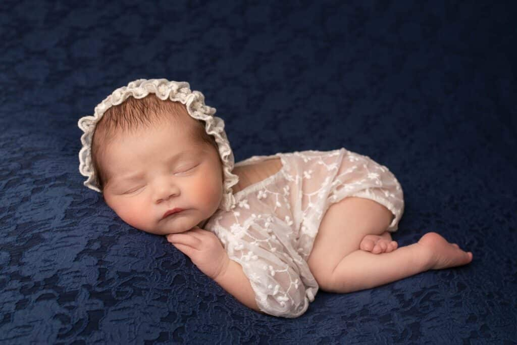 Newborn girl wearing a lace romper and bonnet, sleeping on a blue lace cloth.