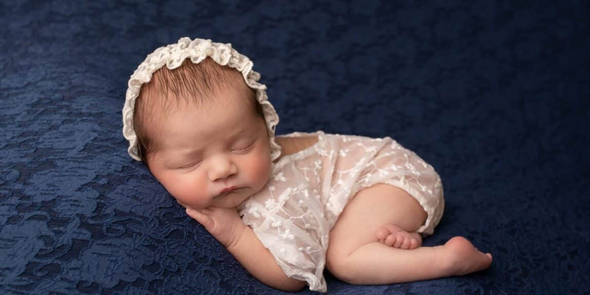 Newborn baby in lace on blue drop