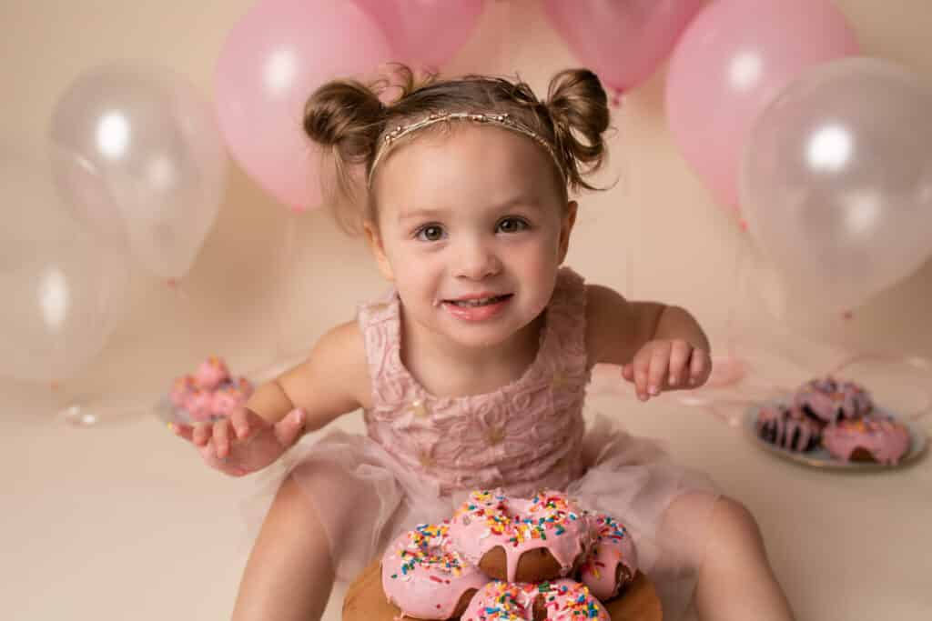 Little girl in pink dress leans forward and smiles with pink balloons behind her and pink sprinkled donuts on a tray in front of her.