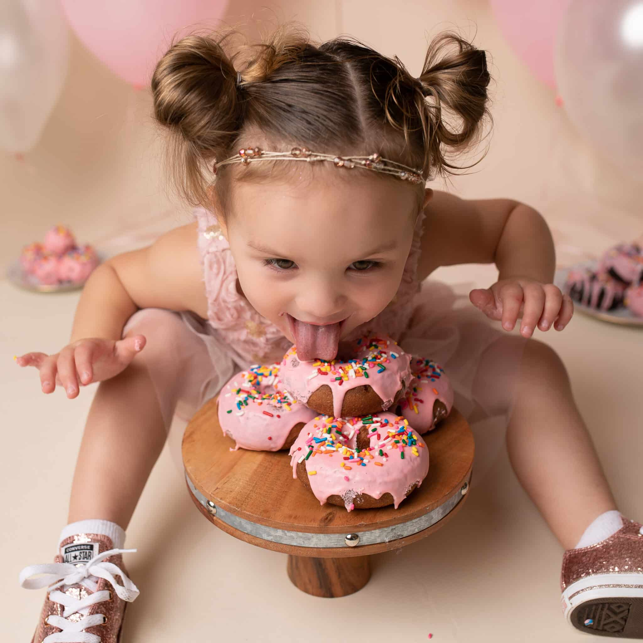 Baby Girl in Pink Dress eating Pink Sprinkled Donuts