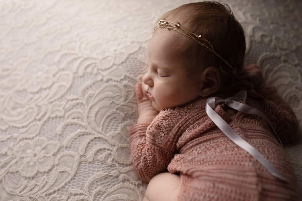 Sleeping baby girl all curled up wearing a pink romper