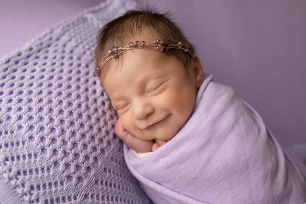 Newborn girl wrapped in purple, smiling while sleeping.