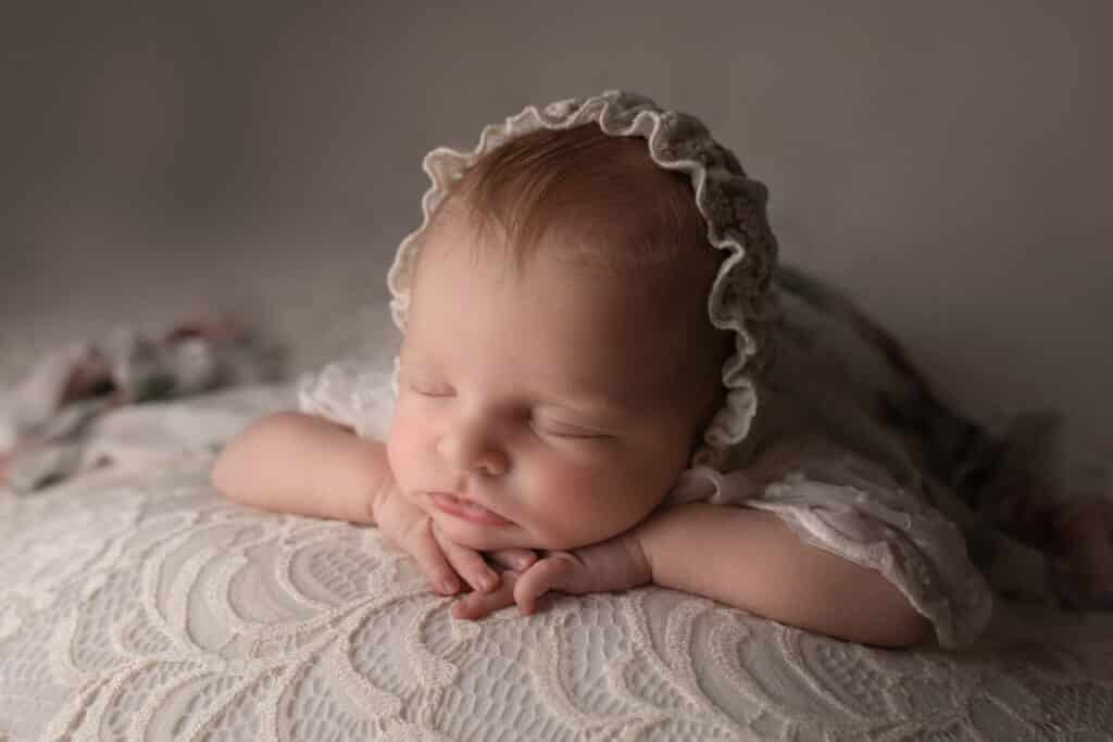 Baby sleeping with chin on hands wearing a lace bonnet.