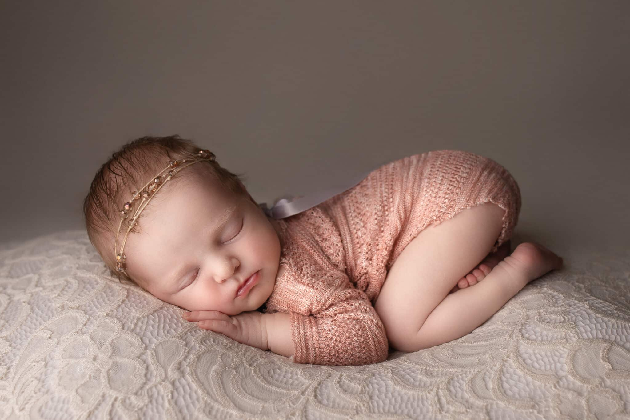 Newborn baby girl wearing a coral pink romper sleeping on a cream lace fabric.